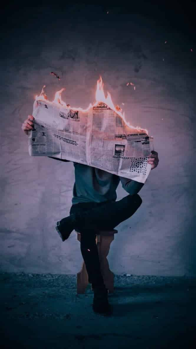 Photo of man reading burning newspaper... Fired.